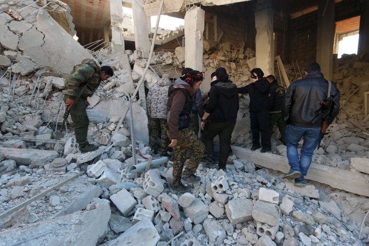 Image: YPG fighters inspect damage at a site hit by one of three truck bombs