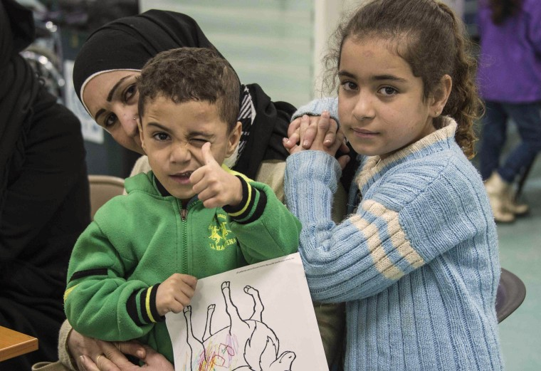 Image: Two Syrian refugee children pose while their family undergoes medical screening before the beginning of an airlift to Canada, in Beirut
