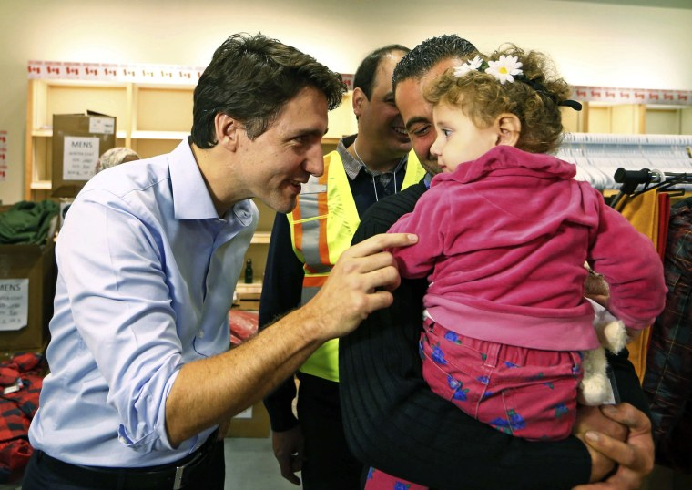 Image: Syrian refugees are greeted by Canada's Prime Minister Justin Trudeau on their arrival from Beirut at the Toronto Pearson International Airport