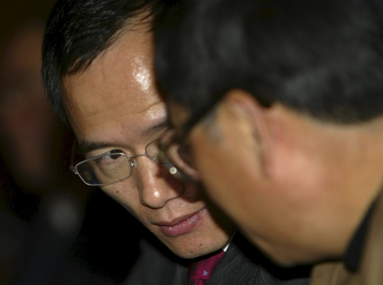 Image: File photo of Guo Guangchang, Chairman of Fosun International, speaking with a man during a conference in Shanghai