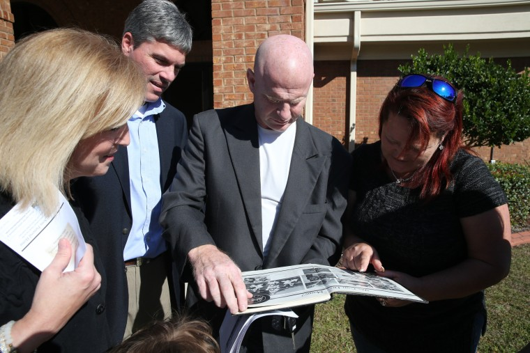 Image: Friends view yearbook pictures of San Bernardino shooting spree victim Shannon Johnson after his funeral at Calvary Baptist Church in Jesup, Georgia