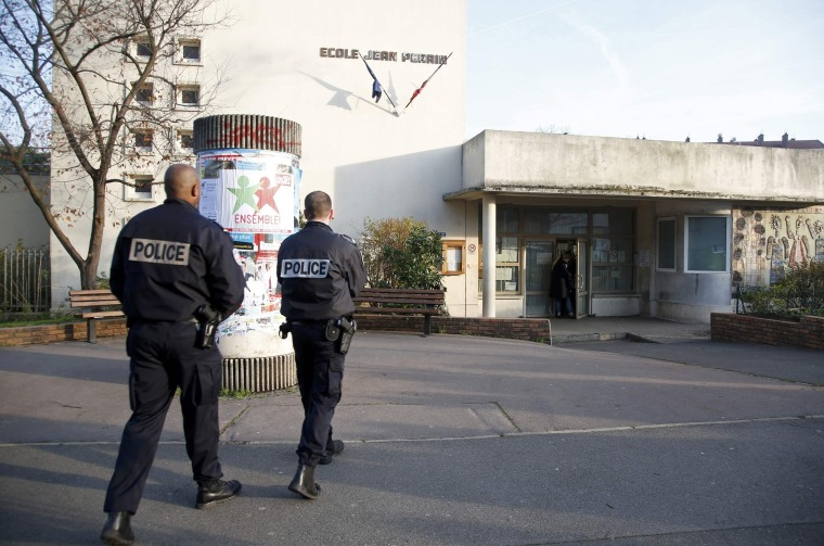 Police stand in front of the nursery school where a hooded man attacked a  teacher with a knife near Paris, Monday.