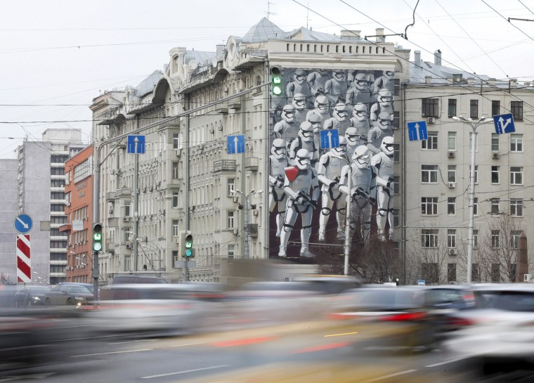Image: Cars drive past a building decorated with a mural depicting Stormtroopers characters from the movie Star Wars in Moscow, Russia
