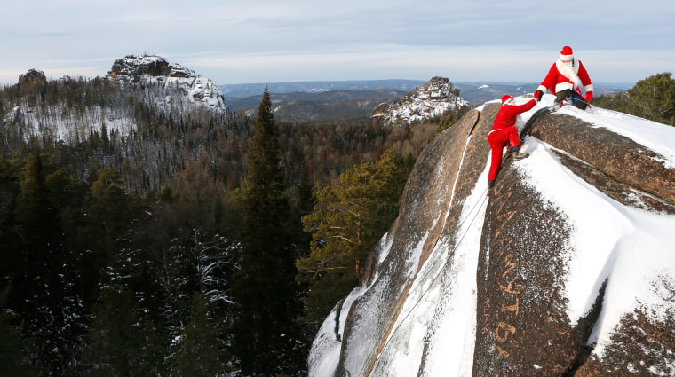 Image: Rescuers dressed as Santa Claus and Father Frost climb at Stolby National Nature Reserve during a training session of Russian Emergencies Ministry outside Krasnoyarsk