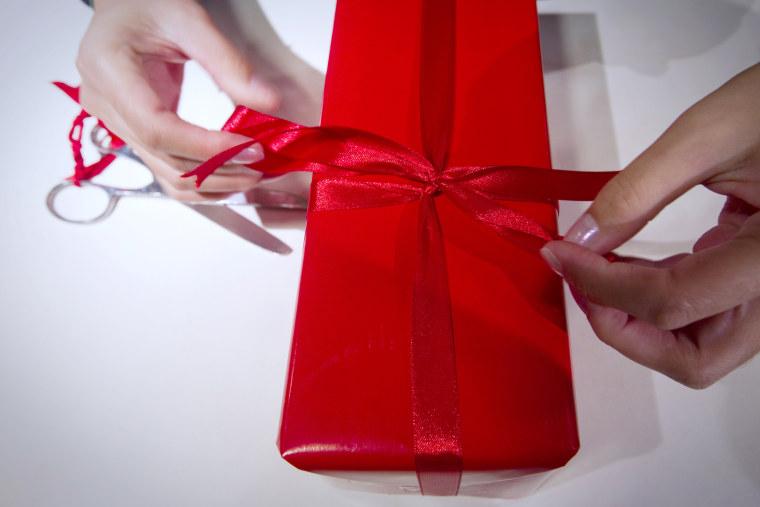 Image: A seller wraps a gift in a Parisian depa