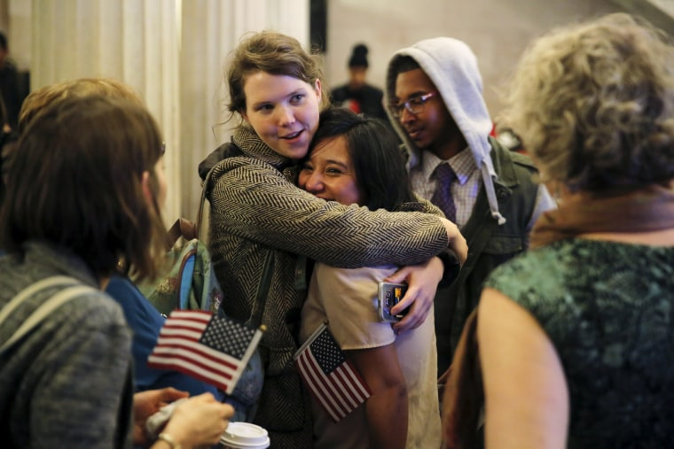 Image: Friends and family surround a newly naturalized citizen after a naturalization ceremony in the Brooklyn borough of New York