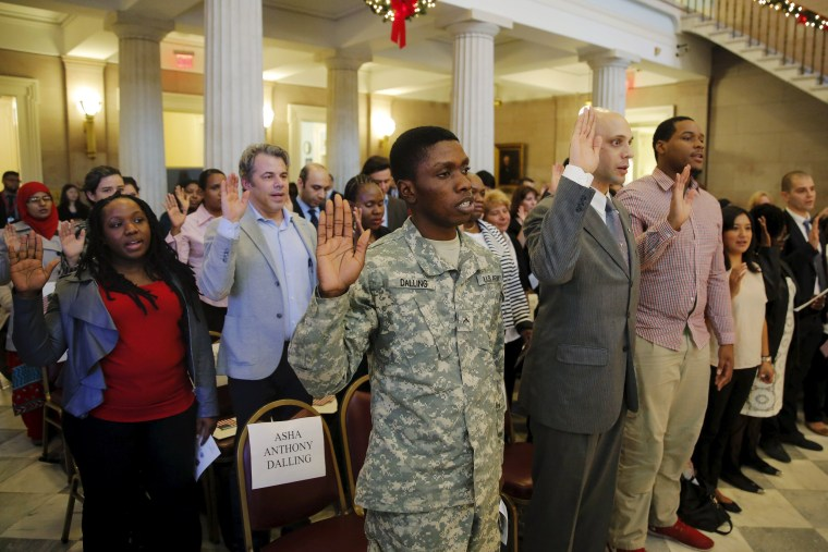Image: U.S. Army Private Asha Dalling (C) raises his hand as he takes the United States Oath of Citizenship during a naturalization ceremony in the Brooklyn borough of New York