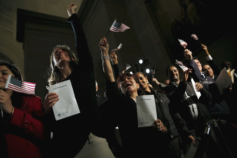Image: People celebrate as they become U.S. citizens during a naturalization ceremony at the National Archives Museum in Washington