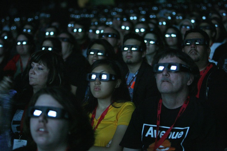 Image: Visitors wear 3D glasses as they watch a movie