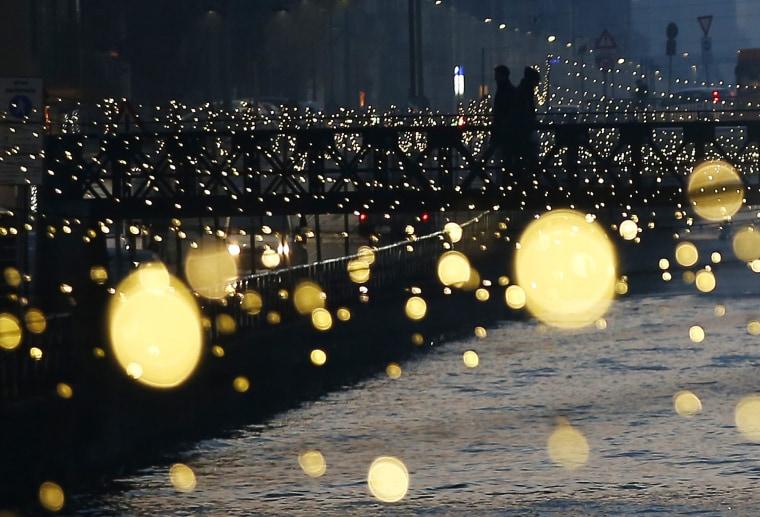 Image: People walk on a bridge as Christmas lights illuminate the Darsena dei Navigli