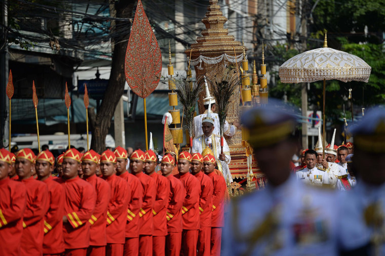 Image: Men in ceremonial uniforms use ropes to pull a carriage transporting the royal urn c
