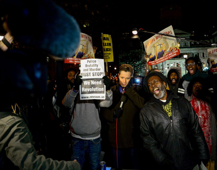 Image: Protesters gather around a CBS television crew outside city hall in Baltimore