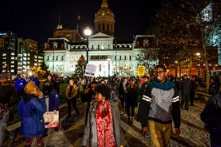 Image: Protesters march at city hall in Baltimore