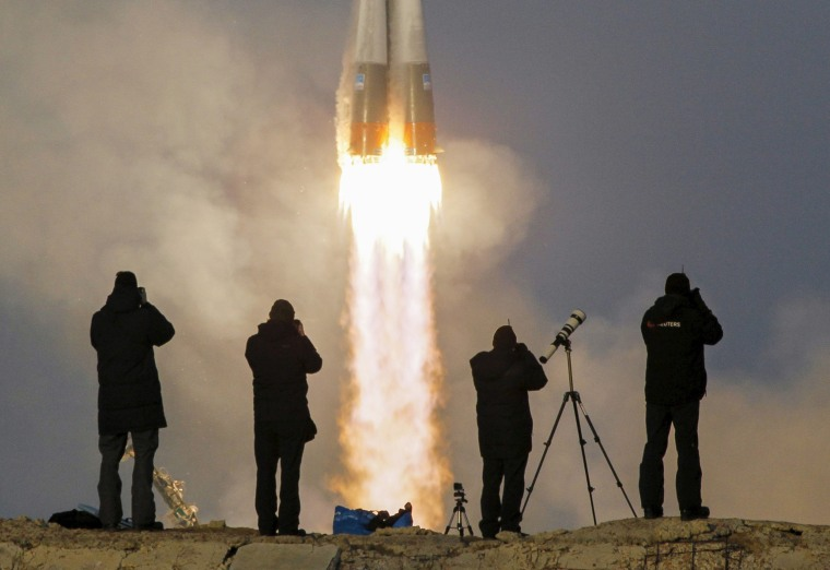 Image: Photographer take pictures as the Soyuz TMA-19M spacecraft carrying the the international Space Station crew as it blasts off from the launchpad at the Baikonur cosmodrome, Kazakhstan