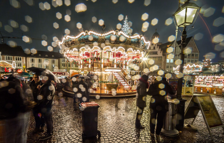 Image: A merry-go-round is seen through a raindrops covered lens