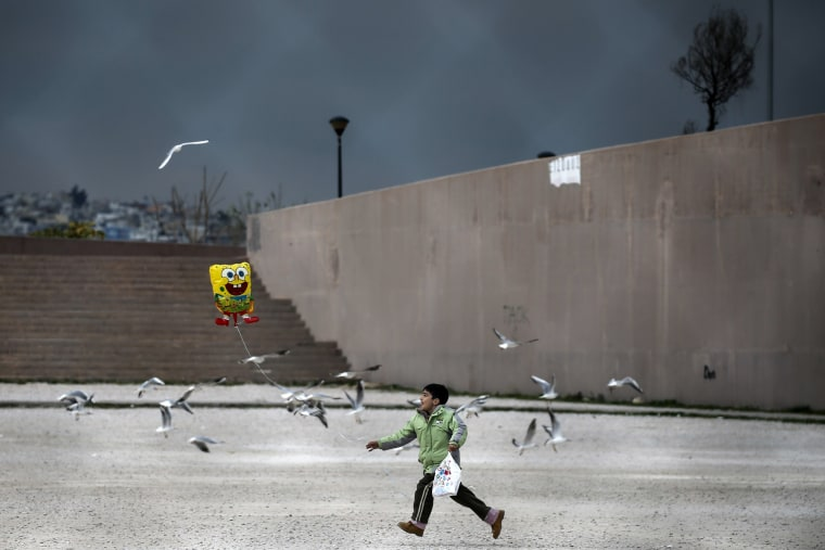 Image: A migrant boy runs while holding a balloon outside the Tae Kwon Do stadium at the southern suburb of Faliro in Athens