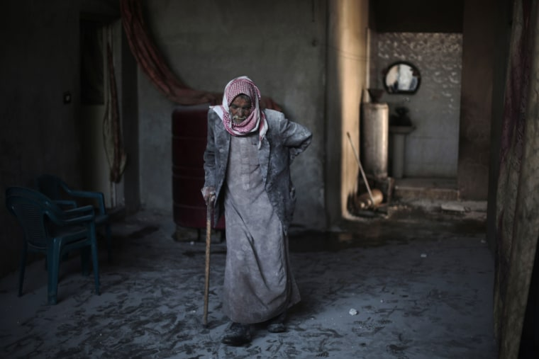 Image: Syrian Abu Mohammed, covered with dust from explosions, walks in his home following reported air strikes