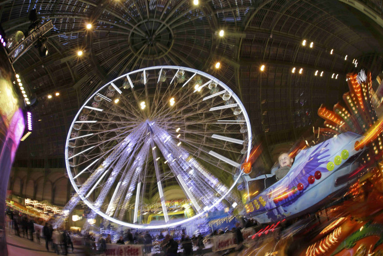 "Image: People enjoy rides at the funfair ""Jours de Fetes"" inside the Grand Palais in Paris"