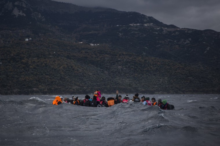 Image: Refugees and migrants on a dinghy approach the Greek island of Lesbos