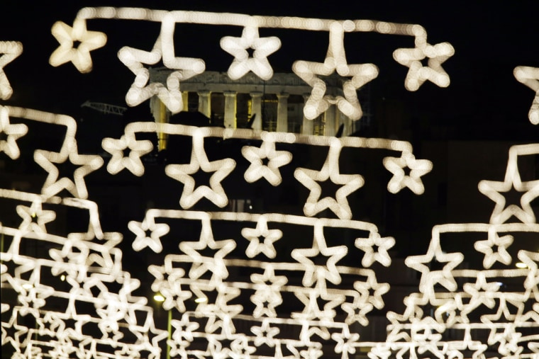 Image: The spotlit ancient Parthenon temple on the Acropolis appears behind strings of Christmas lights in central Athens
