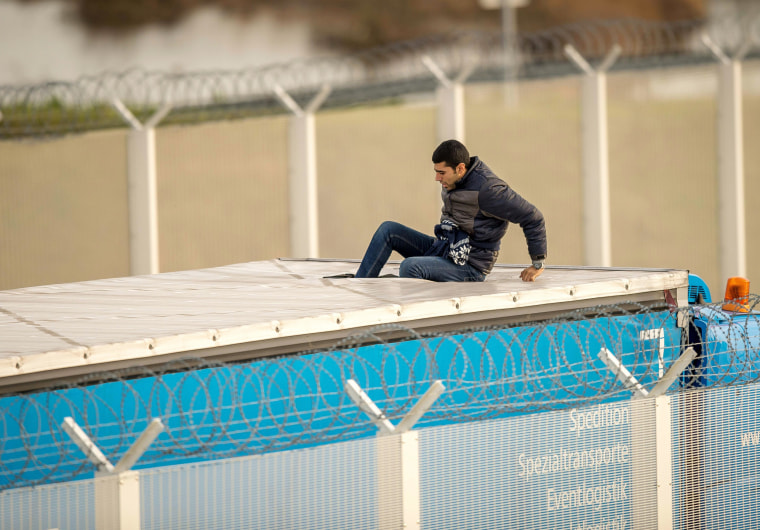 Image: A migrant or refugee enters the trailer of a truck