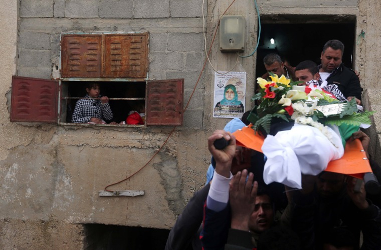 Image: Mourners carry the body of Palestinian woman Samah Abdullah