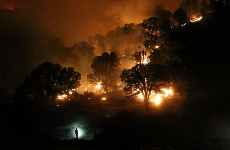 Image: A Cal Fire firefighter is silhouetted by his headlamp as he monitors a backfire