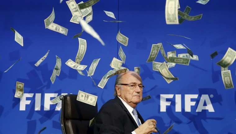 Image: British comedian known as Lee Nelson (unseen) throws banknotes at FIFA President Blatter as he arrives for a news conference after the Extraordinary FIFA Executive Committee Meeting at the FIFA headquarters in Zurich