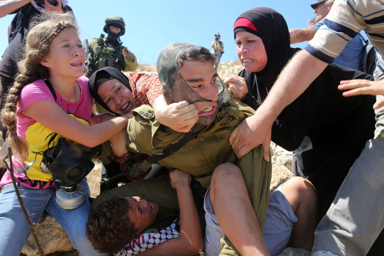 Image: Palestinians fight to free a Palestinian boy held by an Israeli soldier