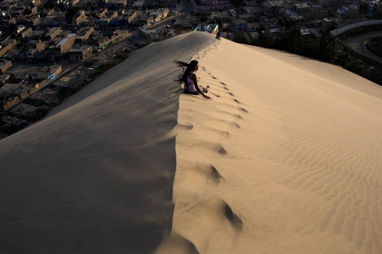 Image: A woman waits for a friend while climbing the Cerro de Saraja