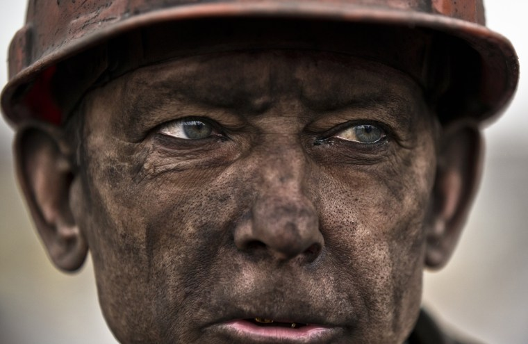 Image: A Ukrainian coal miner waits for a bus after exiting the underground of the Zasyadko mine