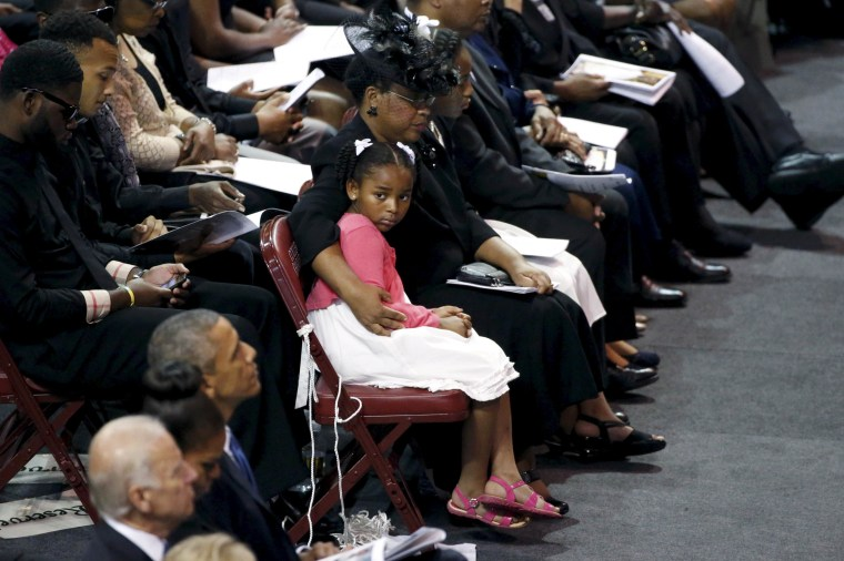 Image: Malana Pinckney, daughter of Reverand Clementa Pinckney, is hugged by her mother Jennifer at the start of her father's funeral in South Carolina