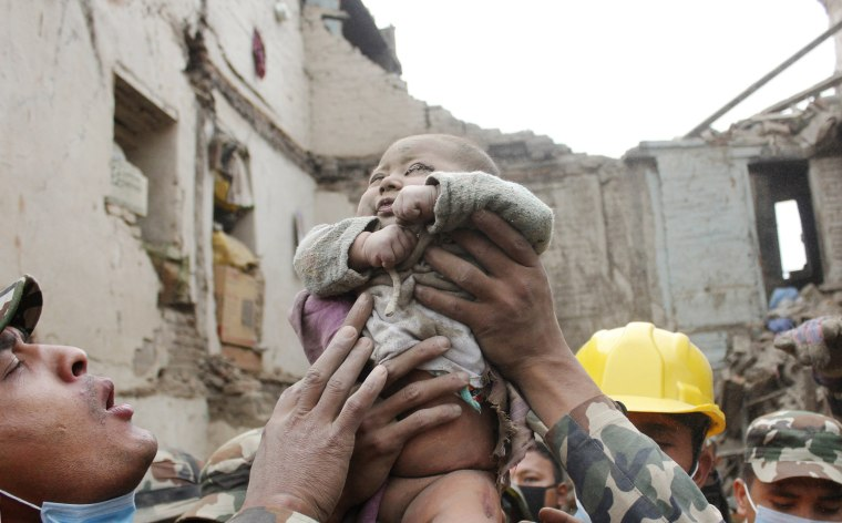 Image: Sonit Awal is held up by Nepalese Army soldiers after being rescued from the rubble of his house