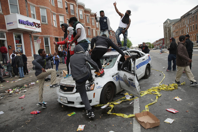 Image:  Demonstrators climb on a destroyed Baltimore Police car in the street