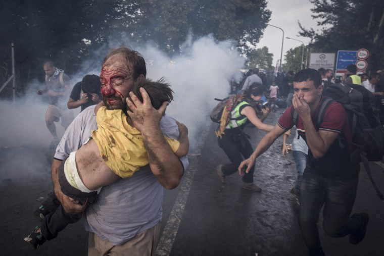 Image: A migrant holds his child during a clash with Hungarian riot police at the Horgos border crossing in Serbia.