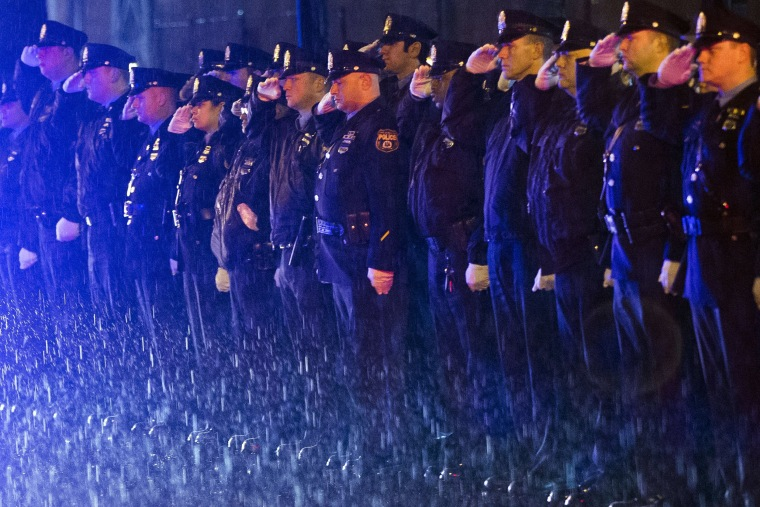 Image: Law enforcement officers salute the arrival of the remains of Philadelphia Police Officer Robert Wilson III