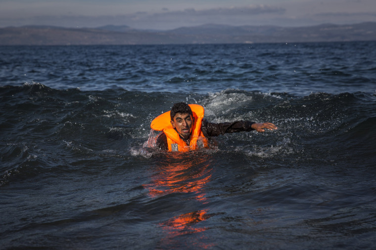 Image: A migrant swims as he arrives on the island of Lesbos after crossing the Aegean sea