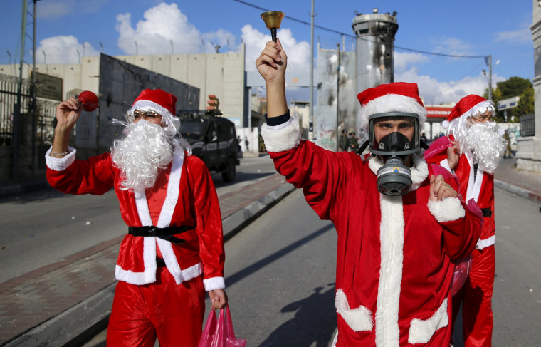 Image: Palestinian protesters wearing Santa Claus costumes take part in an anti-Israel protest in front of the Israeli barrier in the West Bank city of Bethlehem