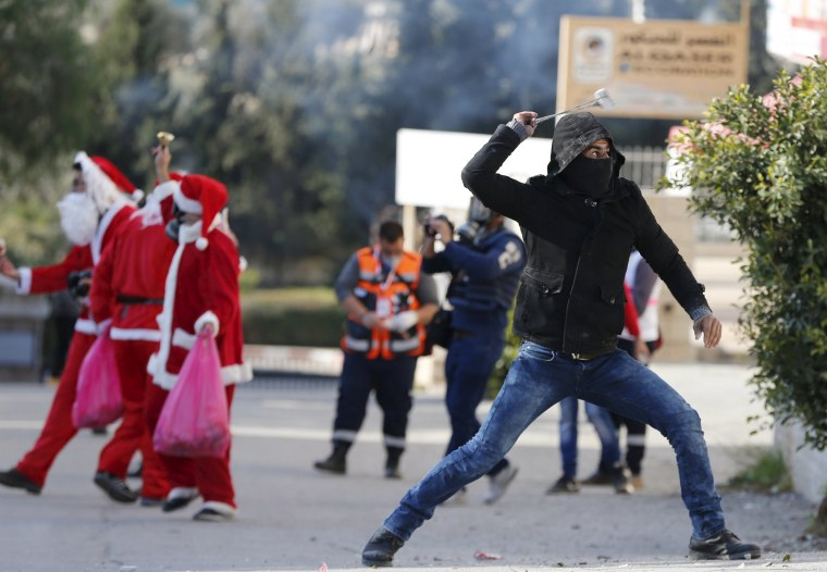 Image: Palestinian protester uses a sling to hurl stones towards Israeli troops during clashes following an anti-Israel protest in the West Bank city of Bethlehem