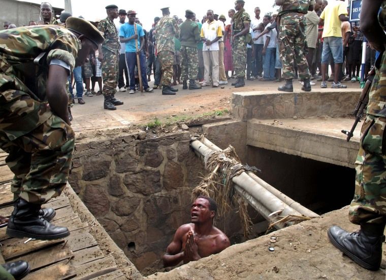 Image: A man begs for help from the military as he stands in a drain