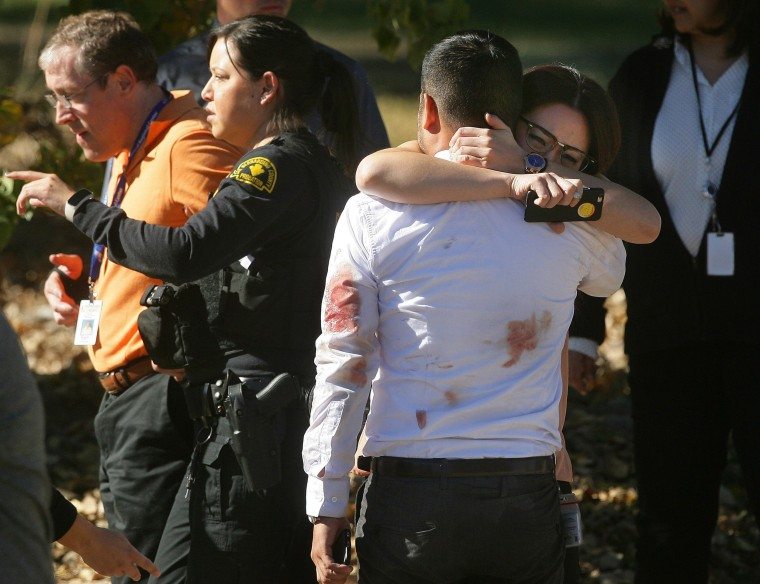 Image: A couple embraces following a shooting that killed multiple people