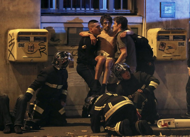 Image: French fire brigade members aid an injured individual near the Bataclan concert hall