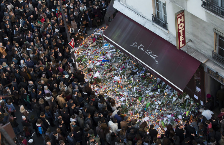 Image: A large crowd gathers to lay flowers and candles in front of the Carillon restaurant in Paris