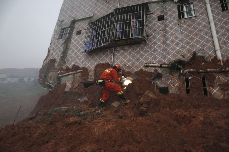 Image: A firefighter uses a flashlight to search for survivors at a damaged building at the site of a landslide at an industrial park in Shenzhen