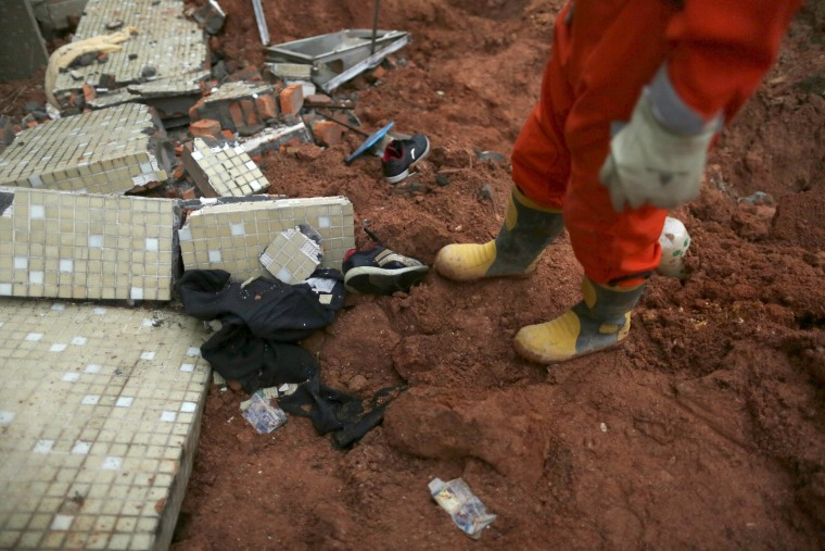 Image: A pair of shoes and other belongings are seen near a damaged building as rescuers search for survivors at the site of a landslide at an industrial park in Shenzhen