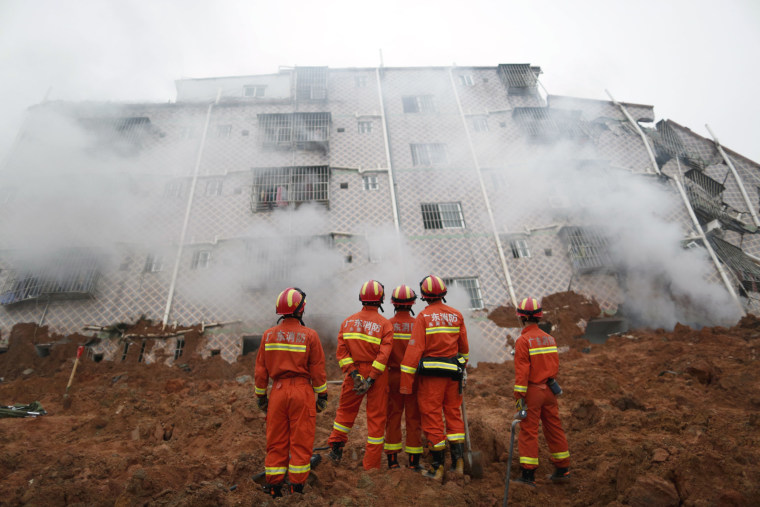 Image: Firefighters look on as smoke rises in front of a damaged building at the site of a landslide at an industrial park in Shenzhen
