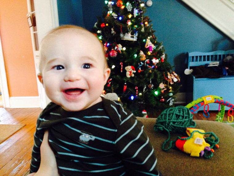 Baby smiling in front of a real Christmas tree