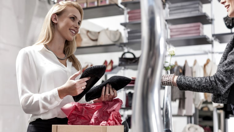 Shop assistant and customer in a shoe shop; Shutterstock ID 316971635; PO: today.com