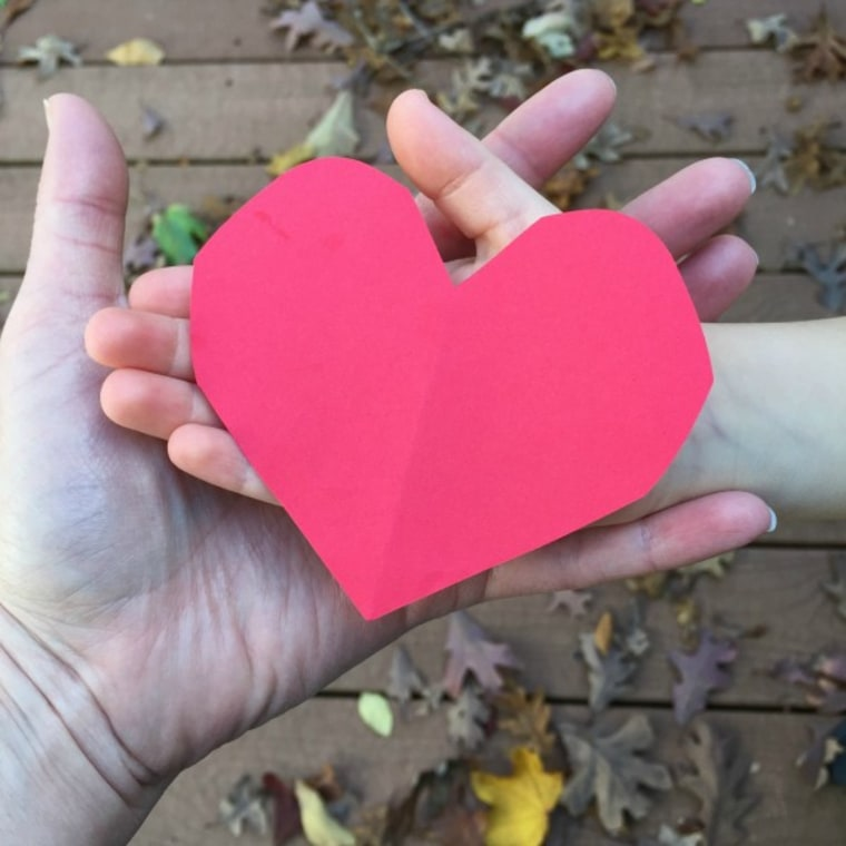 Red paper heart in hands