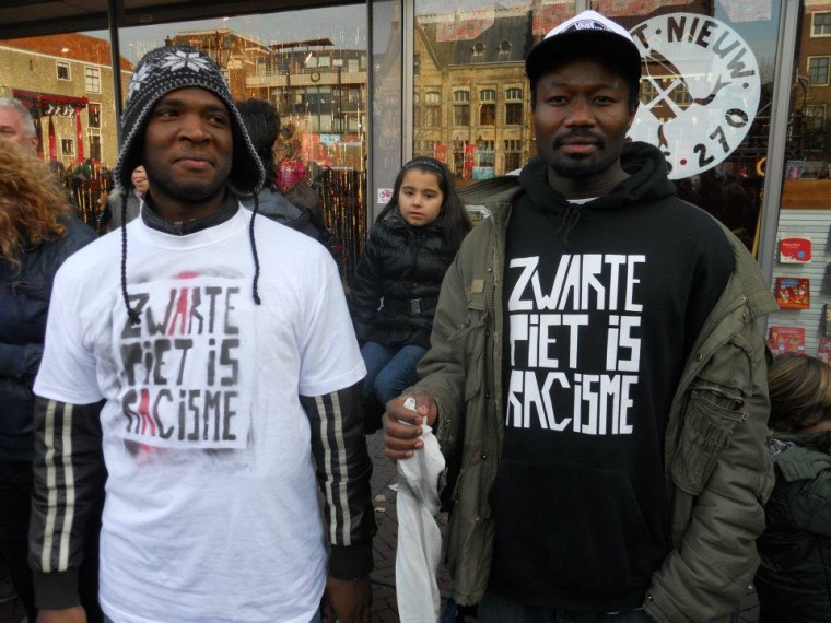 Quinsy Gario (left) and Jerry Afriyie (right) in silent protest at a 2011 Sinterklaas parade in the city of Dordrecht. Their violent arrests during the festivities for wearing t-shirts that read 'Black Pete is Racist' the resistance to Black Pete to the mainstream
